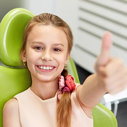 Smiling child giving thumbs up